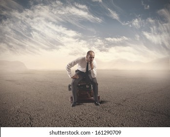 Concept of lost businessman confused sitting on suitcases