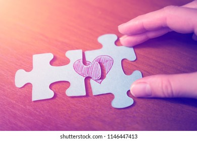 The concept of love. Puzzles of the heart. Hands connect the two halves of the heart.