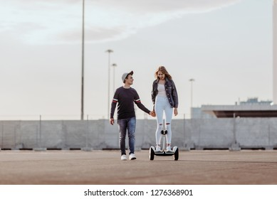 Concept of love relationships man and woman. Lovely couple parked near the stadium in a big city, hugging, kissing and riding a hoverboard. learn to ride a electric hoverboard from afar