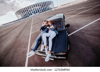Concept of love relationships man and woman. Lovely couple parked near the stadium in a big city, hugging, kissing near their old car. lying on the hood of his old car