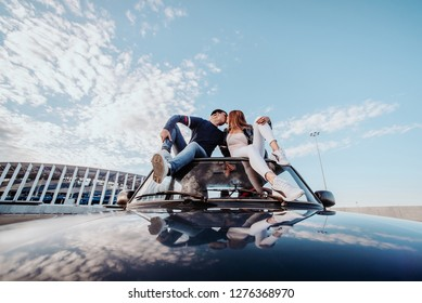 Concept of love relationships man and woman. Lovely couple parked near the stadium in a big city, hugging, kissing near their old car. kiss on the roof of the car