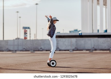 Concept of love relationships man and woman. Lovely couple parked near the stadium in a big city, hugging, kissing and riding a hoverboard. Girl learn to ride a electric hoverboard from afar