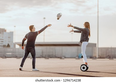 Concept of love relationships man and woman. Lovely couple parked near the stadium in a big city, hugging, kissing and riding a hoverboard. throws a cap view