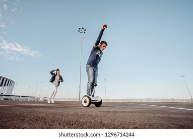 Concept of love relationships man and woman. Lovely couple parked near the stadium in a big city, hugging, kissing and riding a hoverboard. Man learn to ride a electric hoverboard from afar
