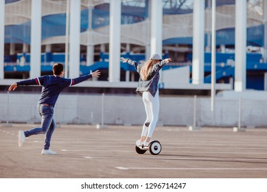 Concept of love relationships man and woman. Lovely couple parked near the stadium in a big city, hugging, kissing and riding a hoverboard. Girl learn to ride a electric hoverboard from afar view