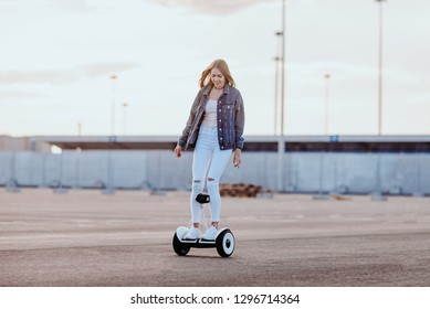 Concept of love relationships man and woman. Lovely couple parked near the stadium in a big city, hugging, kissing and riding a hoverboard. Girl learn to ride a electric hoverboard horizontal