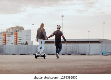 Concept of love relationships man and woman. Lovely couple parked near the stadium in a big city, hugging, kissing and riding a hoverboard. learn to ride a electric hoverboard
