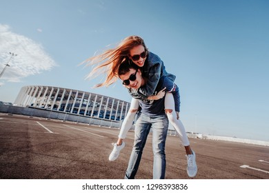 Concept of love relationships man and woman. Lovely couple parked near the stadium in a big city, hugging, kissing and enjoying each other. girl riding a guy on the background of the stadium close