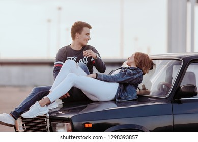 Concept of love relationships man and woman. Lovely couple parked near the stadium in a big city, hugging, kissing near their old car. lying on the hood of his old car close