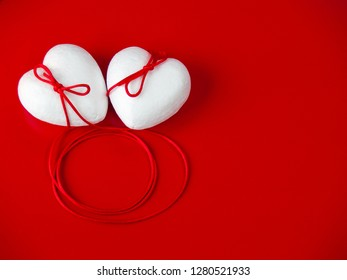 Concept of love Two poliespan hearts joined with a red thread that symbolizes the legend of the red thread