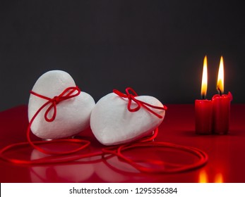 Concept of love Two poliespan hearts joined with a red thread that symbolizes the legend of the red thread and two red lit candles