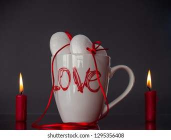 Concept of love Two poliespan hearts joined with a red thread that symbolizes the legend of the red thread on a breakfast cup and two red lit candles