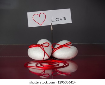 Concept of love Two poliespan hearts joined with a red thread that symbolizes the legend of the red thread and one card with the text love
