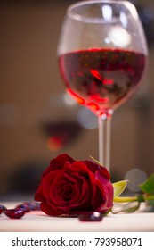 The concept of Love, Wedding, Proposal, Anniversary. A romantic evening with a glasss of red wine and a beautiful red velvet rose. Dark blurred background