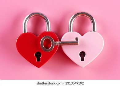 The concept of male treason. Two heart shaped locks and one key on a pink background.