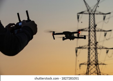 A concept of a man flying a drone collecting a data remotely from a power tower station or for telecommunication. Drone safety, power lines.