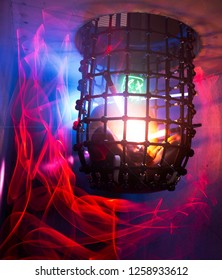 Concept: Man with a scary mask stuck in a cage with light painting.