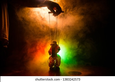 Concept of manipulation. Hand holds strings for manipulation. The hand controls the puppet strings on a dark foggy background. Selective focus