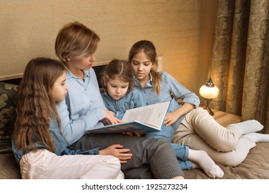 the concept of maternal love and care. a mother with many children reads a book to her children in the evening in the bedroom. reading fairy tales for daughters