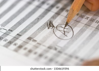 Concept of measurement and evaluation. Hand of teacher using pencil written text on paper of final grades for each course. The number of grade points student earned in given period of time of school.