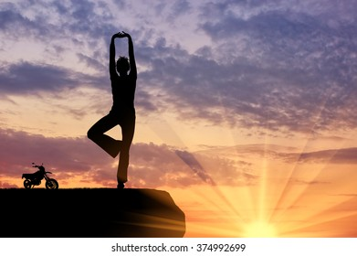 Concept of meditation and relaxation. Silhouette of a girl practicing yoga exercise on the sunset background