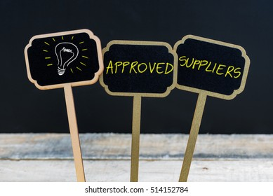 Concept message APPROVED SUPPLIERS and light bulb as symbol for idea written with chalk on wooden mini blackboard labels, defocused chalkboard and wood table in background