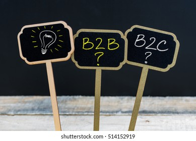 Concept message B2B as Business To Business, B2C as Business To Consumer and light bulb as symbol for idea written with chalk on wooden mini blackboard labels,  chalkboard and wood table in background