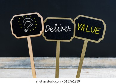 Concept message DELIVER VALUE and light bulb as symbol for idea written with chalk on wooden mini blackboard labels, defocused chalkboard and wood table in background