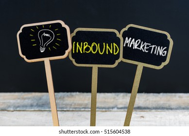 Concept message INBOUND MARKETING and light bulb as symbol for idea written with chalk on wooden mini blackboard labels, defocused chalkboard and wood table in background