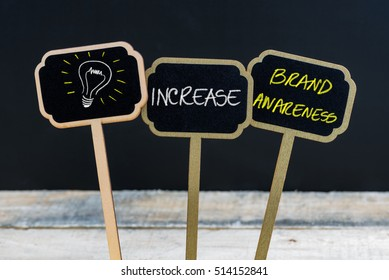 Concept message INCREASE BRAND AWARENESS and light bulb as symbol for idea written with chalk on wooden mini blackboard labels, defocused chalkboard and wood table in background