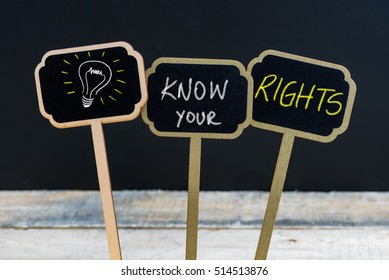 Concept message KNOW YOUR RIGHTS and light bulb as symbol for idea written with chalk on wooden mini blackboard labels, defocused chalkboard and wood table in background