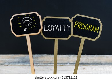 Concept message LOYALTY PROGRAM and light bulb as symbol for idea written with chalk on wooden mini blackboard labels, defocused chalkboard and wood table in background