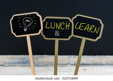 Concept message LUNCH and LEARN and light bulb as symbol for idea written with chalk on wooden mini blackboard labels, defocused chalkboard and wood table in background