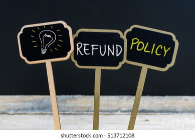 Concept message REFUND POLICY and light bulb as symbol for idea written with chalk on wooden mini blackboard labels, defocused chalkboard and wood table in background