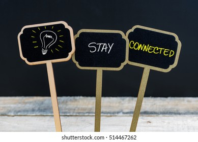 Concept message STAY CONNECTED and light bulb as symbol for idea written with chalk on wooden mini blackboard labels, defocused chalkboard and wood table in background