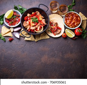 Concept of Mexican food.  Salsa, tortilla, beans, fajitas and tequila. Top view.