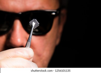 The concept of military artificial intelligence and machine learning .A man in black glasses holds a microchip.