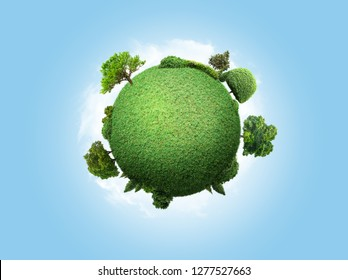 concept miniature globe showing the environment with trees and grass on sky background