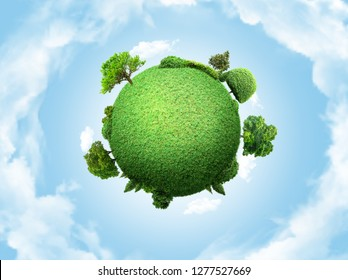 concept miniature globe showing the environment with trees and grass on cloudy sky background