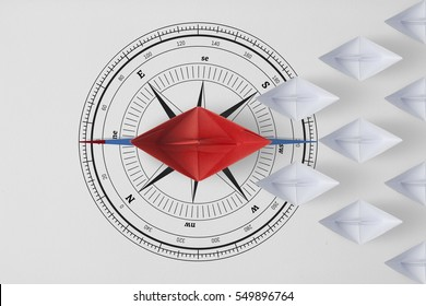 Concept  minimal vision leadership teamwork and workforce leader management with red paper ship on compass needle pointing in front of leading among paper ship white.