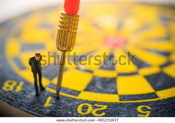 Concept of missed target business strategy. Businessman looking at the untargeted arrow on dart board.