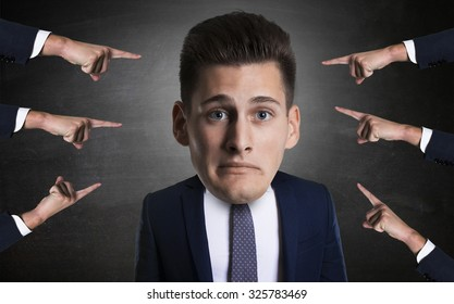 concept of mobbing with portrait of a young employee with many arms pinting at him.