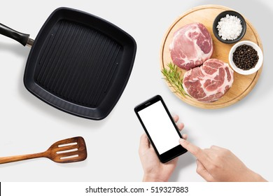 Concept of mockup using smartphone and raw pork chop steak, grill pan and spatula set isolated on white background. Clipping Path included on white background.