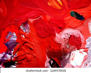 the concept of modern art. abstract background. palette with paint close-up. rich red and pink shades. the paint is applied in large strokes