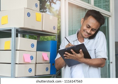 Concept modern new asian entrepreneur. E-commerce business owner calling to supplier to confirm order and reviewing checklist of customer address before sent box of product by parcel post.