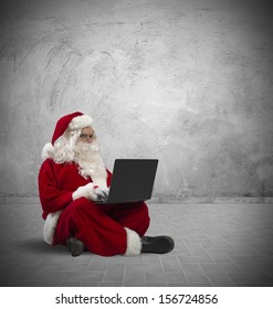Concept of modern Santa Claus with laptop