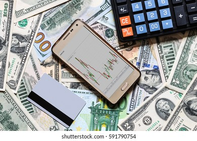 Concept with money american dollar, euro bills, credit card black calculator and mobile phone with the schedule of exchange rates.