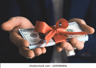 Concept, money as a gift, win or bonus. businessman takes or gives pile of 100 dollar bills tied with red ribbon with bow.