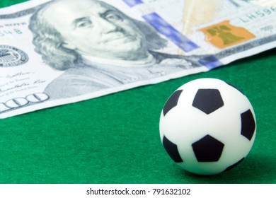 Concept money and sports, betting on football. A small soccer ball on a green background next to a hundred-dollar bill. Macro. Super close-up.