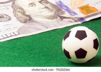 Concept money and sports, betting on football, a player's salary. Macro. A soccer ball on a green background and a hundred-dollar bill. Super close-up.